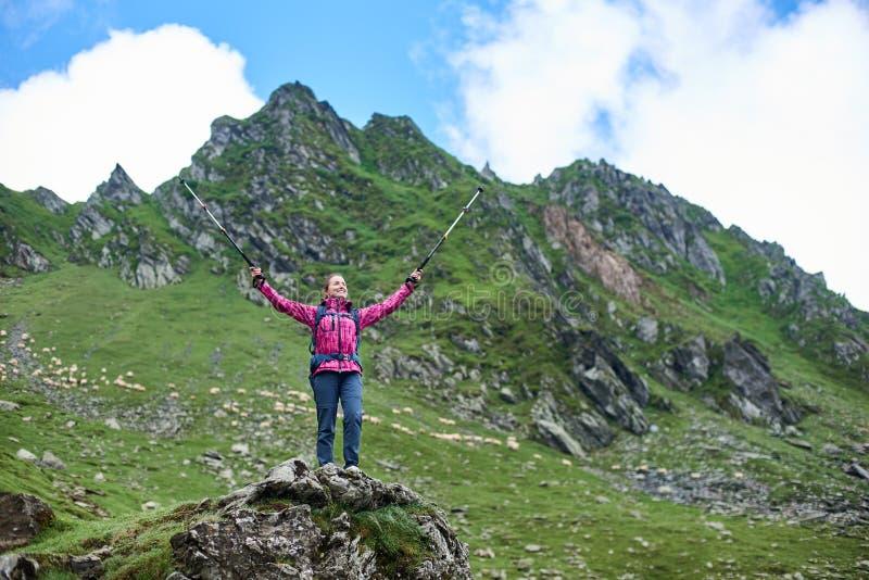 La mujer turística se está colocando en roca en la montaña del pie imagenes de archivo