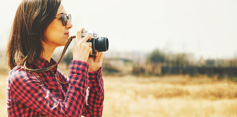 La mujer turística toma las fotografías con la cámara de la foto del vintage imagenes de archivo