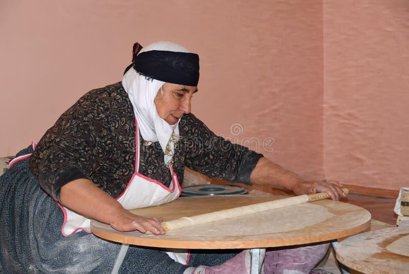La mujer turca hace un pan Pita fotografía de archivo libre de regalías