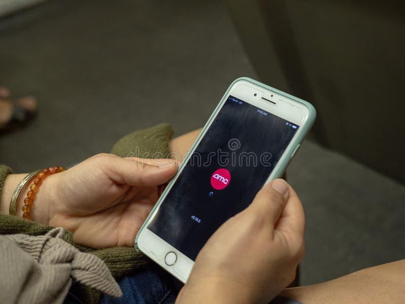 La mujer utiliza el app móvil del cine de AMC en iPhone mientras que conmuta en el metro foto de archivo