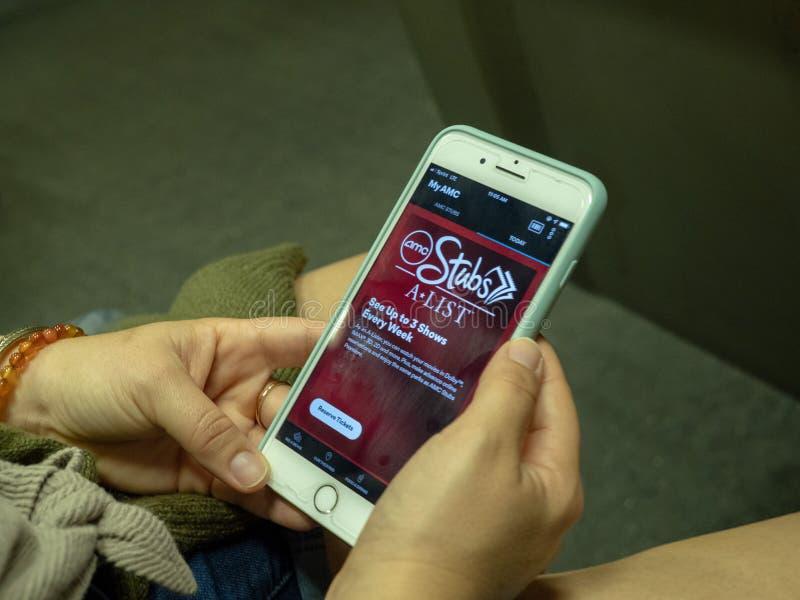 La mujer utiliza el app móvil del cine de la Uno-lista de los trozos de AMC en iPhone mientras que conmuta en el metro imagen de archivo