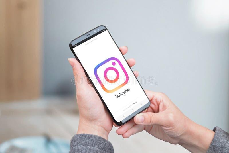 La mujer utiliza el uso de Instagram Logotipo grande de Instagram en la exhibición imagenes de archivo