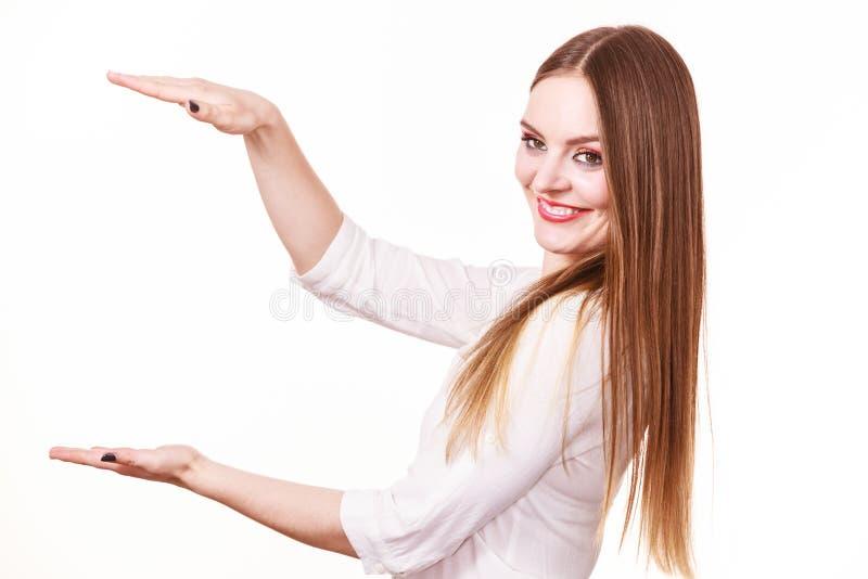 La mujer utiliza las manos para indicar el área del bastidor, copia el espacio para el producto imágenes de archivo libres de regalías