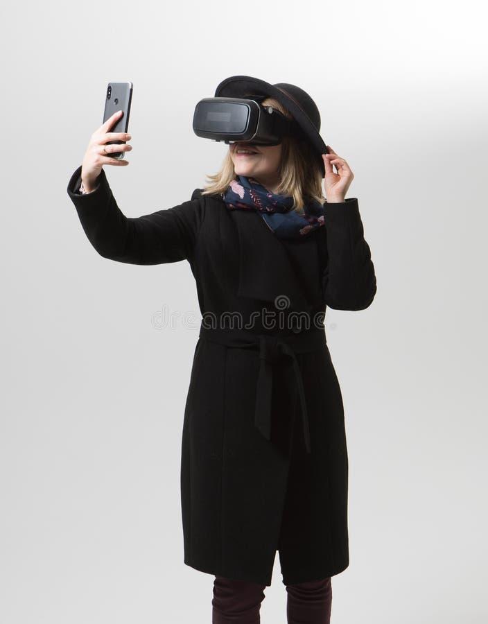 La mujer utiliza los vidrios de una realidad virtual VR 360 Juego virtual fotografía de archivo libre de regalías