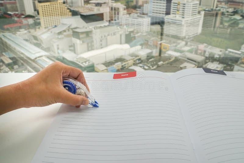 La mujer utiliza la pluma flúida de la corrección en mofa encima de la hoja de papel para el retiro del error imagen de archivo libre de regalías