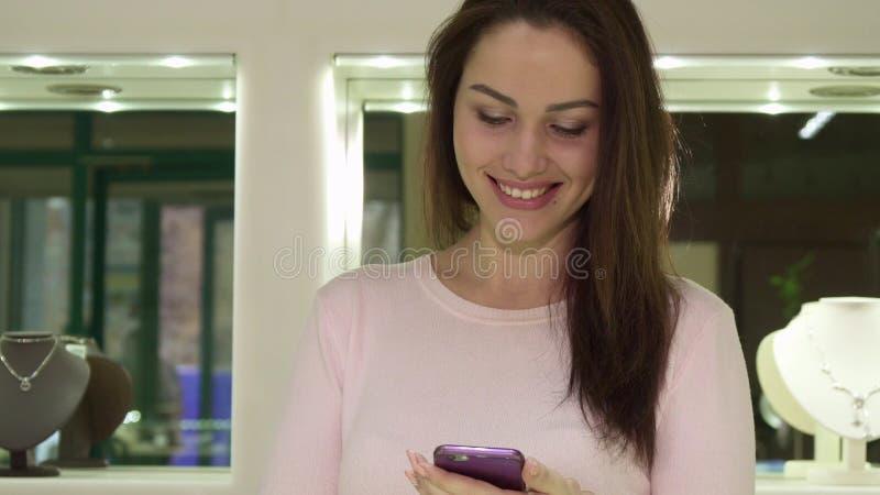 La mujer utiliza su smartphone en jewerly la tienda imagen de archivo libre de regalías