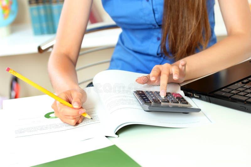 La mujer utiliza una calculadora foto de archivo libre de regalías