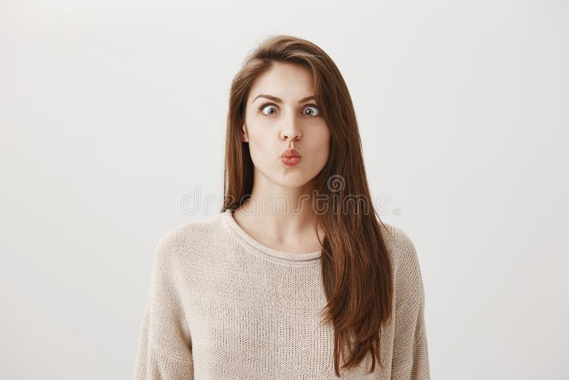 La mujer va loca del aburrimiento Retrato de la muchacha europea infantil divertida que hace caras, bizqueando y frunciendo los l imagenes de archivo