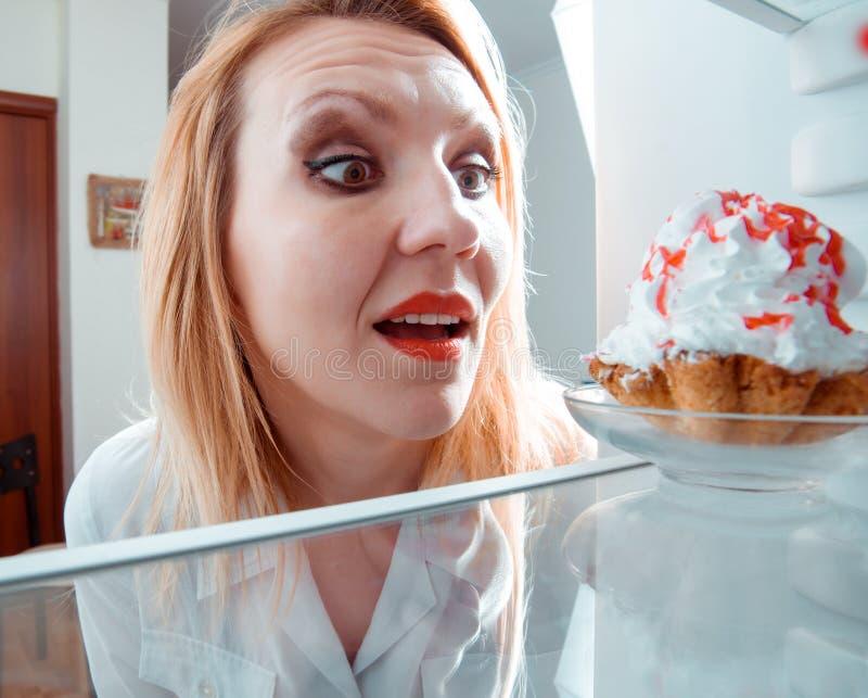 La mujer ve la torta dulce en refrigerador imagenes de archivo