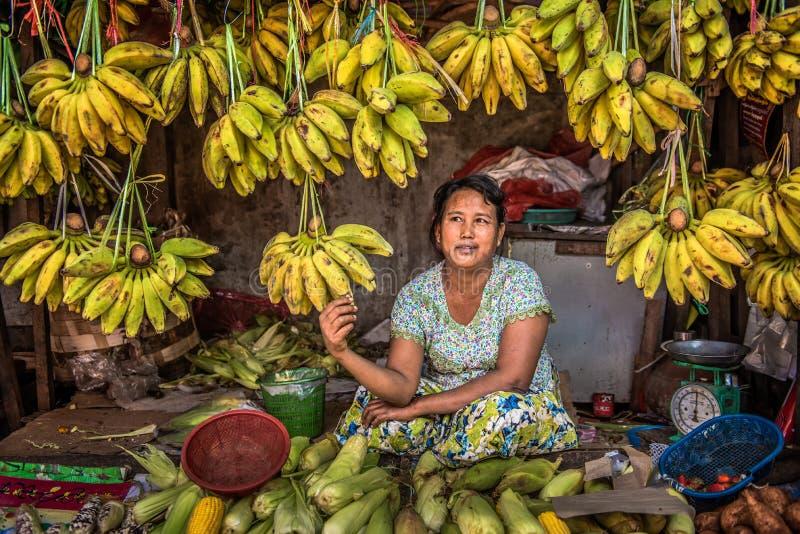 La mujer vende plátanos en un mercado local en Rangún, Myanmar foto de archivo