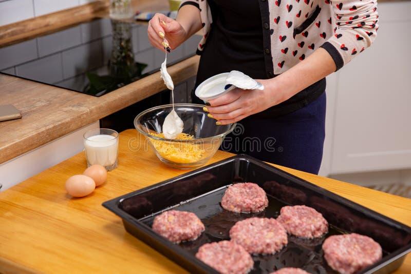 La mujer vierte la crema agria al queso rallado mujeres que cocinan el plato de la carne para asar en el horno imagen de archivo libre de regalías