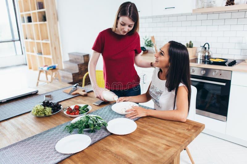 La mujer vierte la leche en el cuenco su amigo en cocina fotografía de archivo