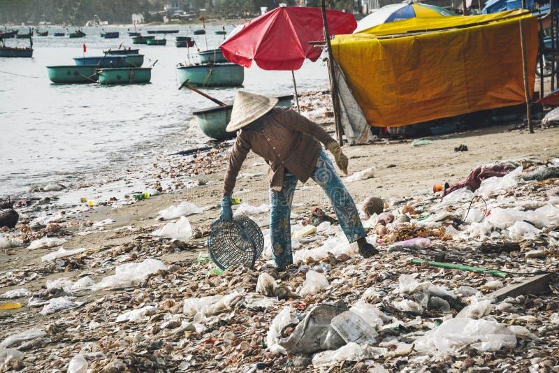 La mujer vietnamita lanza la basura en la playa por el mar Descarga por el mar mala ecolog?a en Asia sudoriental Pueblo de los pe fotos de archivo