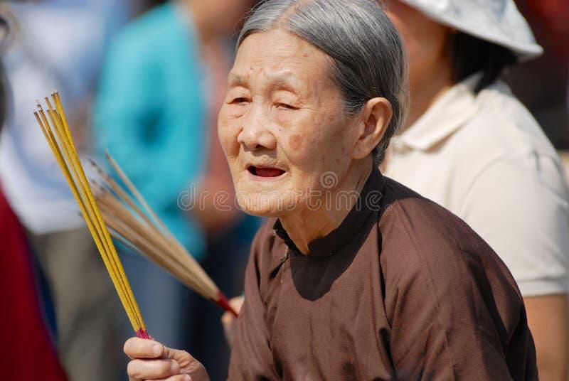 La mujer vietnamita mayor ruega sostener los palillos del incienso en el templo budista durante la celebración china en Ho Chi Mi foto de archivo