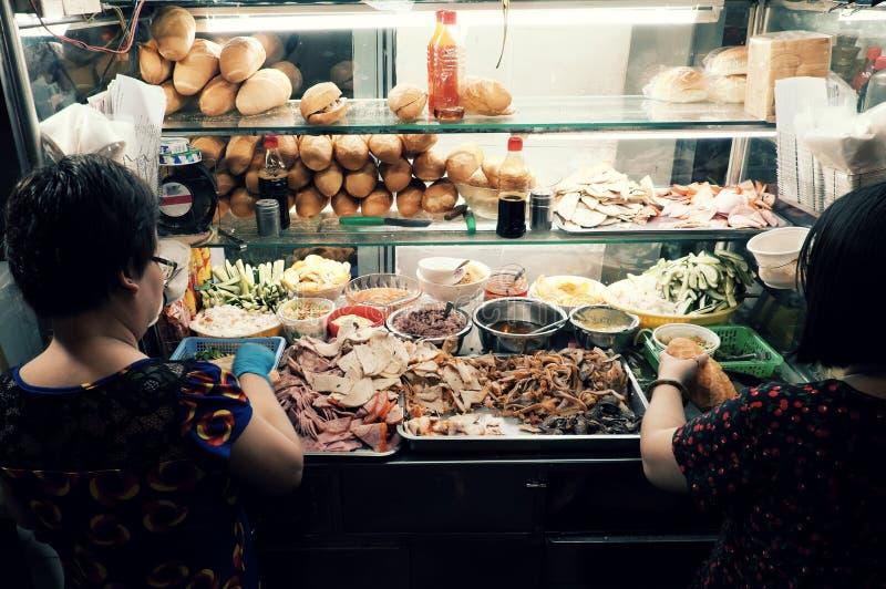 La mujer vietnamita vende el pan de Vietnam en el carro en la comida de la calle de la noche fotografía de archivo libre de regalías