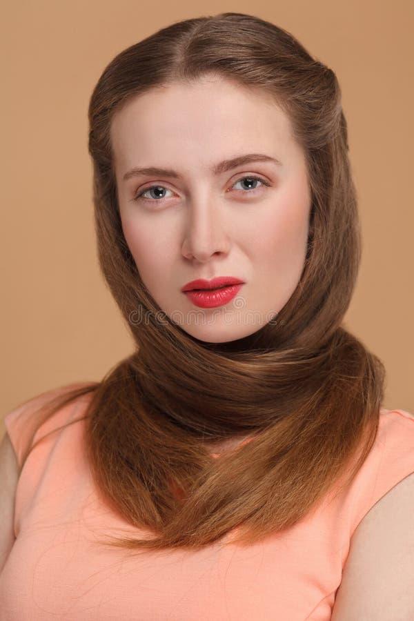 La mujer wraped el pelo alrededor de su cuello y la mirada de la cámara foto de archivo