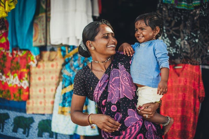 La mujer y el bebé indios no identificados en sus brazos están sonriendo con muy foto de archivo