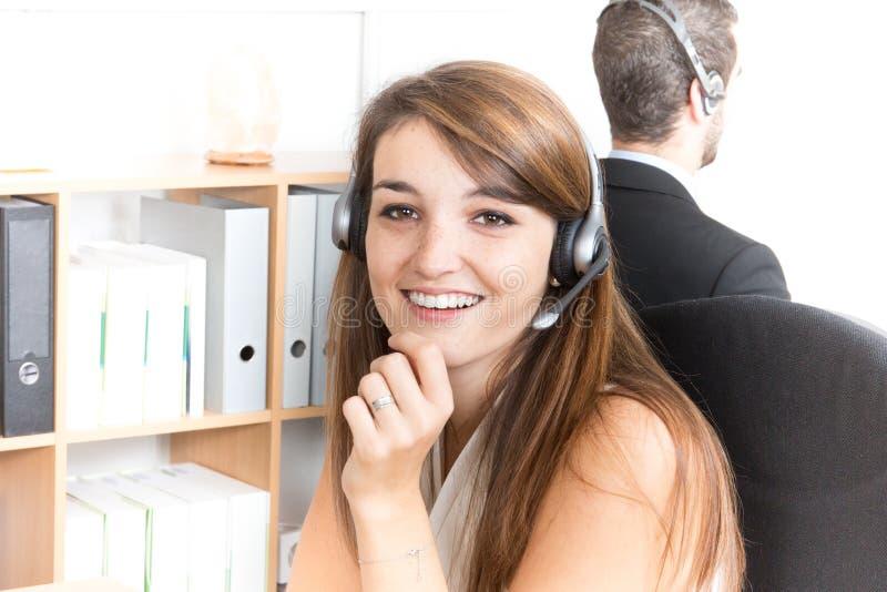 La mujer y el hombre apoyan a operadores del teléfono en auriculares foto de archivo