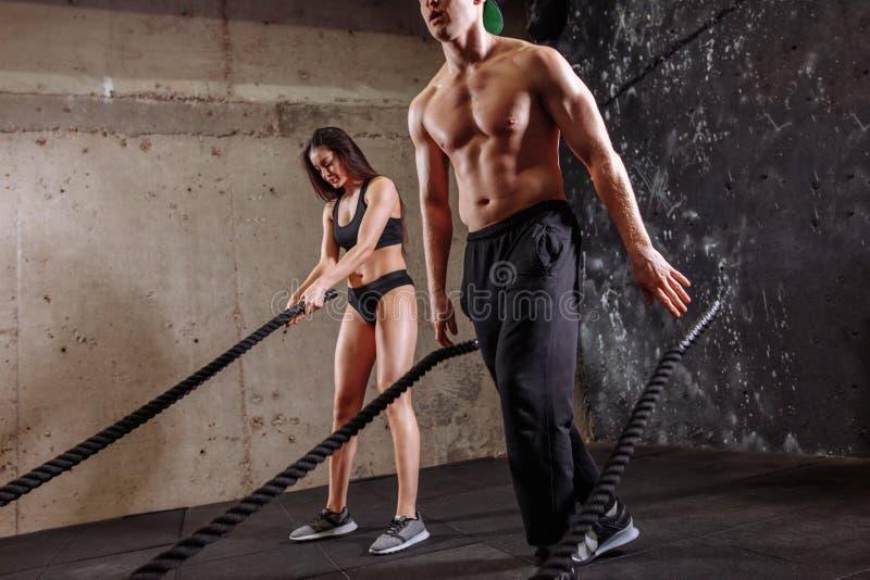 La mujer y el hombre juntan el entrenamiento juntos de hacer entrenamiento de lucha de la cuerda fotografía de archivo libre de regalías