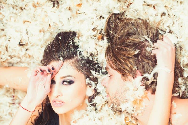 La mujer y el hombre sensuales se relajan en la pluma, amor Mujer con maquillaje y machista durmiente, relaciones Júntese en amor foto de archivo libre de regalías