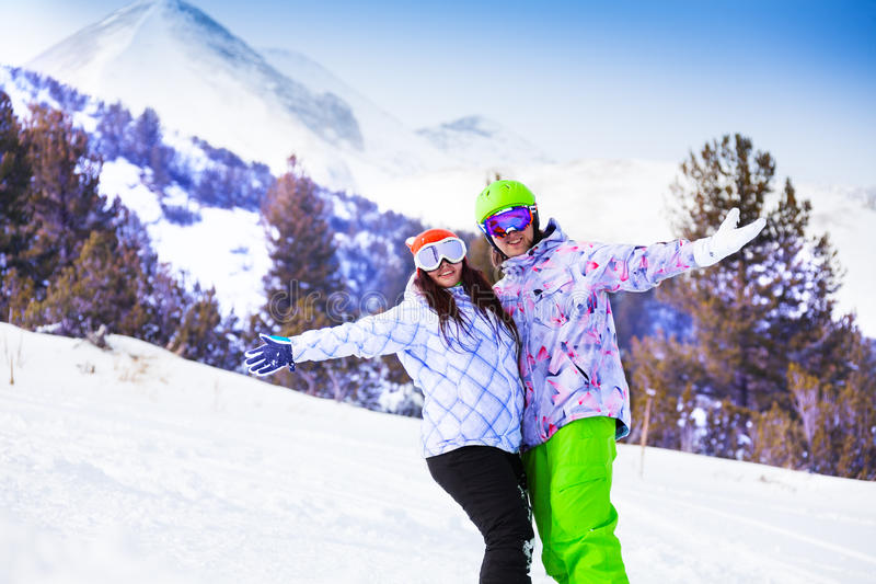 La mujer y el hombre sonrientes en máscaras de esquí abrazan las manos imagen de archivo