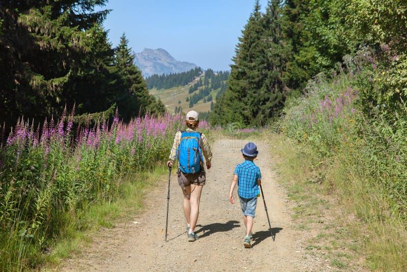 La mujer y el muchacho están caminando en las montañas francesas imágenes de archivo libres de regalías