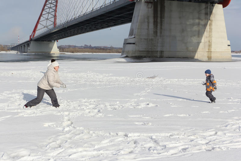La mujer y el niño pequeño que juegan bolas de nieve en el riverbank imágenes de archivo libres de regalías