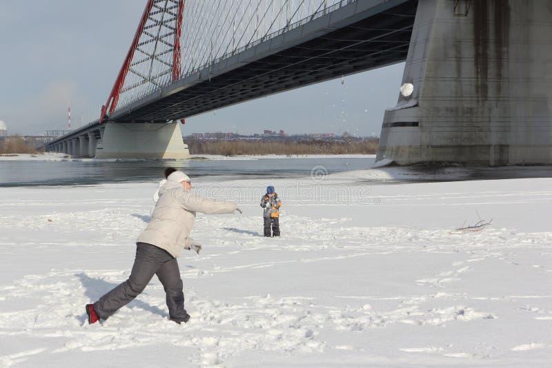 La mujer y el niño pequeño que juegan bolas de nieve en el riverbank imagenes de archivo