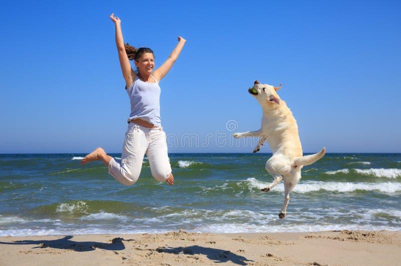 La mujer y el perro crían Labrador que salta en la playa fotos de archivo libres de regalías