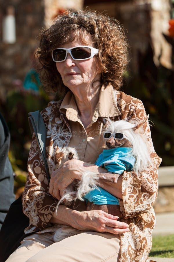 La mujer y el perro sin pelo chino llevan hacer juego las gafas de sol en el acontecimiento imágenes de archivo libres de regalías