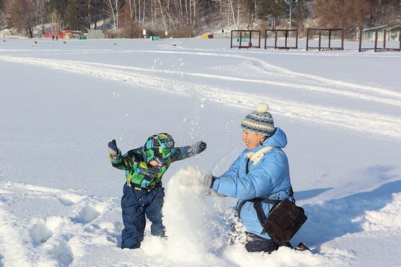 La mujer y la nieve del tiro del niño pequeño imagen de archivo libre de regalías