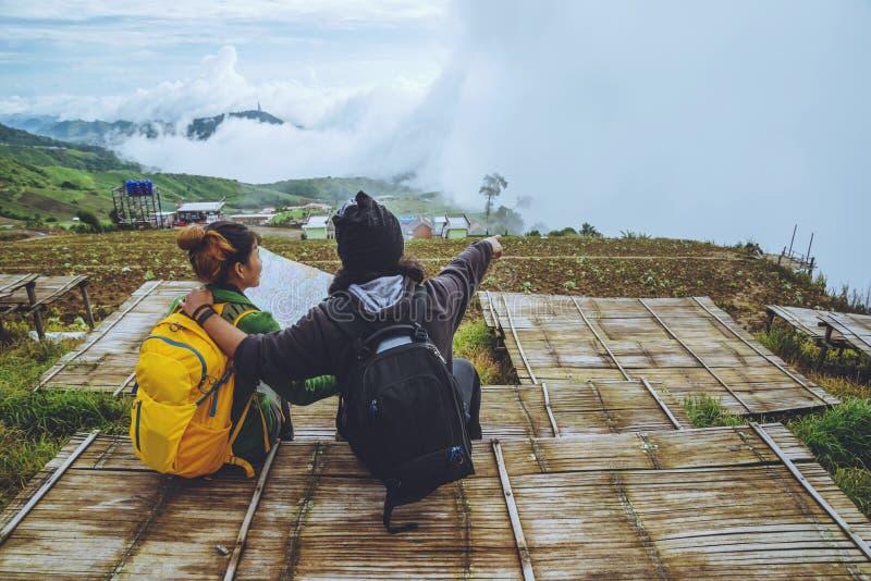 La mujer y los hombres del amante que viajan los asiáticos se relajan en el día de fiesta El mapa de la visión explora las montañ fotos de archivo libres de regalías
