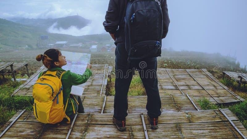 La mujer y los hombres del amante que viajan los asiáticos se relajan en el día de fiesta El mapa de la visión explora las montañ imagen de archivo