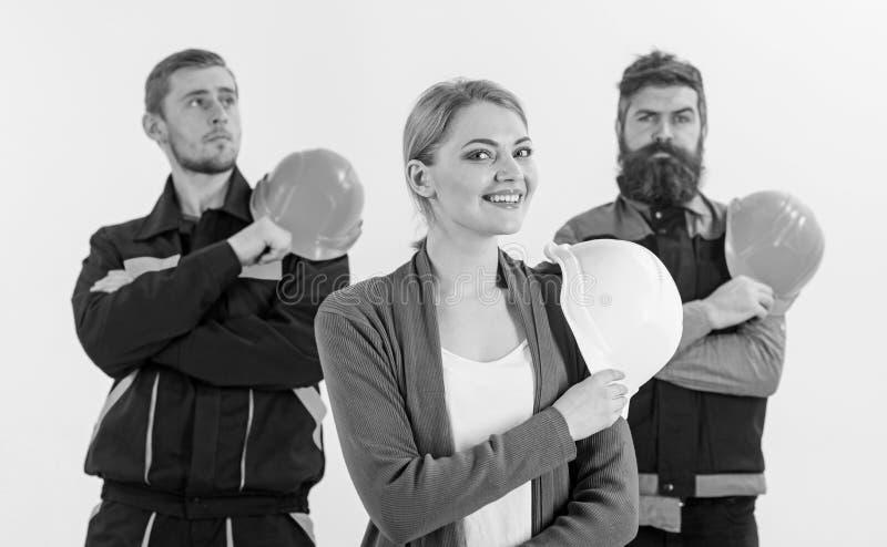 La mujer y los hombres sostiene los cascos Equipo de concepto de los constructores imagen de archivo