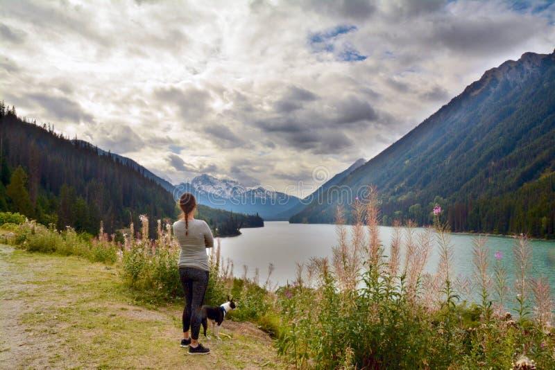 La mujer y su perro de Boston Terrier visitan River Valley en el valle y Duffy Lake Road cerca de marmota, A.C. Canadá de Pembert foto de archivo libre de regalías