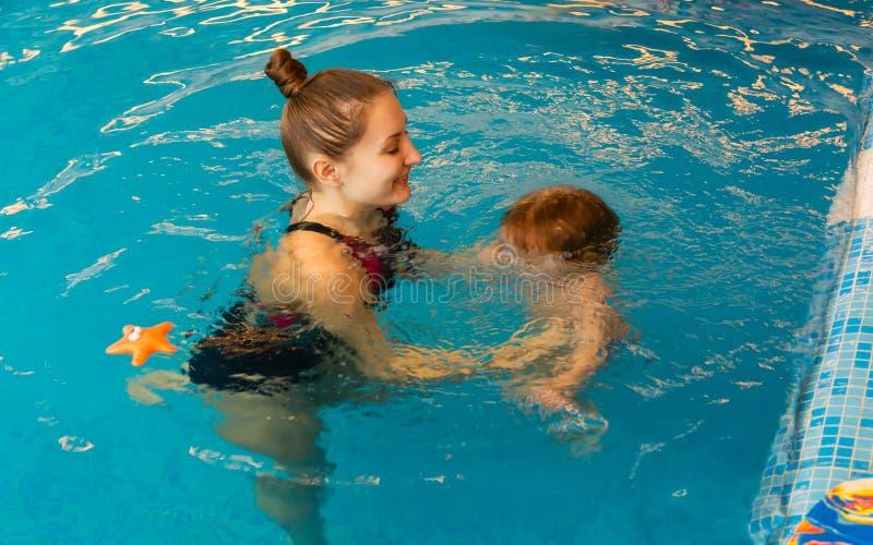 La mummia impara il bambino per galleggiare in stagno fotografie stock