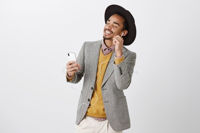La musica allevia dallo sforzo Tipo attraente rilassato soddisfatto in vestito di classe e cappello d'avanguardia, ballanti con g fotografie stock
