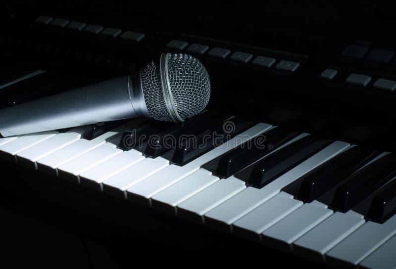 La musica del sintetizzatore nello scuro Microfono fotografia stock libera da diritti