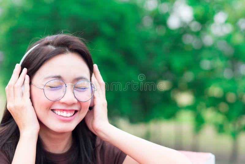 La musique de écoute de femmes de l'Asie et le sourire avec des écouteurs pour détendent images stock