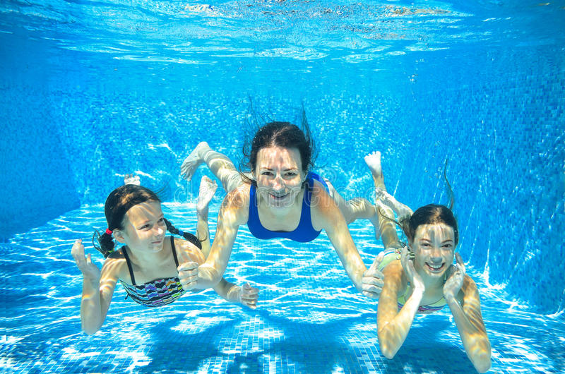 La nadada de la familia en la piscina subacuática, la madre y los niños se divierten en agua, fotos de archivo