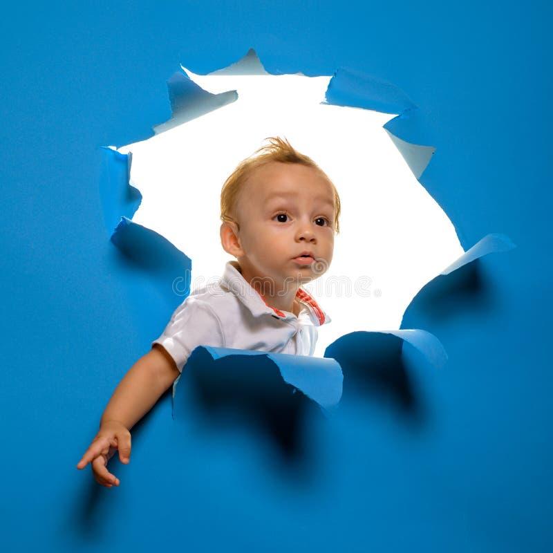 La naissance de la nouvelle vie Regard curieux d'enfant de garçon hors de trou en papier Peu coup d'oeil d'enfant par le papier d photos stock