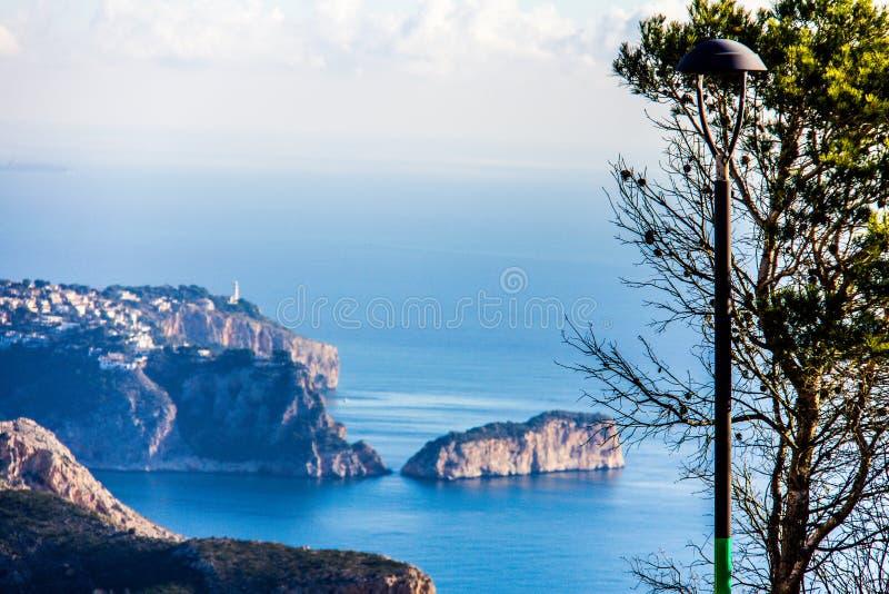 La Nao海角全景在Javea,西班牙 一棵树和街灯在前景 免版税库存照片