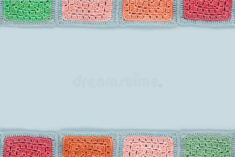 la nappe faite du crochet de dentelle des places multicolores ornementent sur un fond gris, la vue supérieure, endroit pour le te photo stock