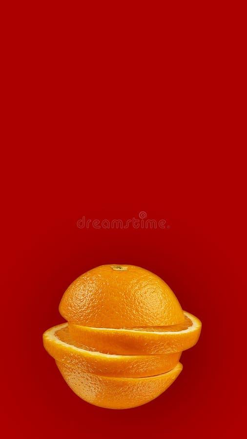 La naranja cortó en un fondo rojo brillante Concepto mínimo de la fruta fotos de archivo libres de regalías