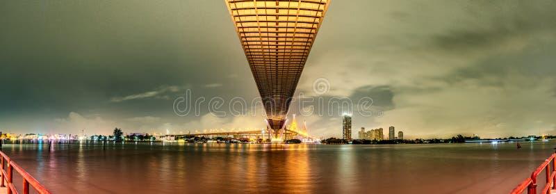 La naranja del panorama llevó la luz debajo del puente sobre el río en un día nublado en el cielo Puente de Bhumibol, Samut Praka fotos de archivo