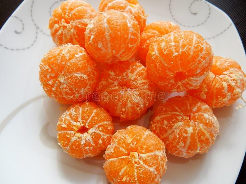La naranja peló las mandarinas en una placa imagen de archivo libre de regalías