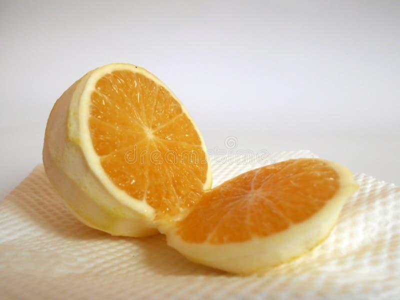La naranja peló y partió en dos aislado en blanco imagen de archivo