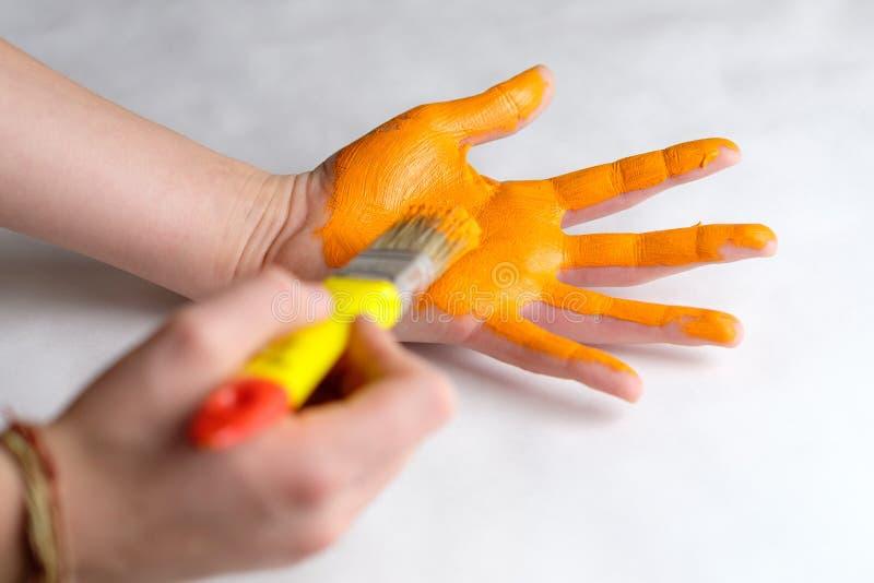La naranja que colorea da la palma, creatividad del ` s de los niños foto de archivo