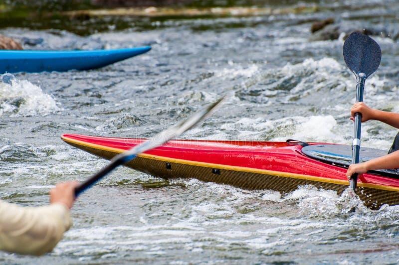 La nariz del kajak y los remos son primer El transportar en balsa en rápidos del río imagenes de archivo