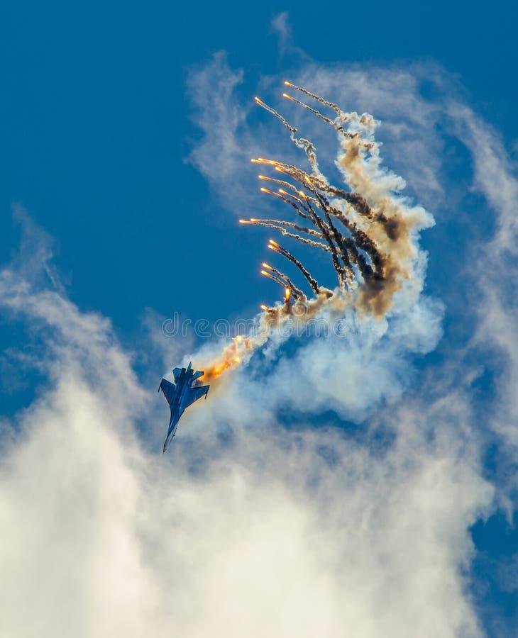 La nariz-zambullida del combatiente SU-27 de los aviones militares, realiza la maniobra con la eyección de los misiles del calor imagenes de archivo